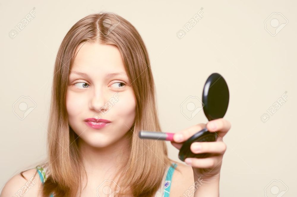 29346269-Happy-teen-girl-holding-lipstick-and-looking-at-the-mirror-Stock-Photo.jpg